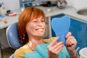 Woman smiling looking at new dental implants in mirror