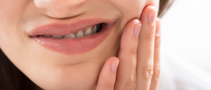 Close-up of young woman in pain from tooth sensitivity