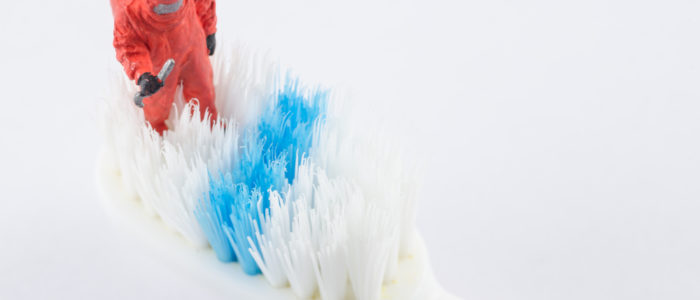 Man in Hazmat Suit Examining an oversized Toothbrush