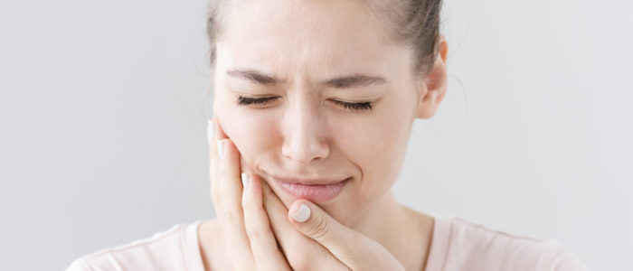 Teenage girl wincing from pain from a toothache