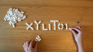 xylitol spelled with white letters and pieces of gum