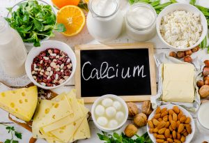 Calcium on a chalk board surrounded by fresh foods