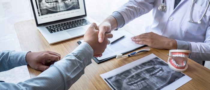 Dentists shaking hands with dental x-ray images in the background