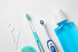 Oral hygiene tools laid out on a white background