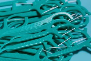 A pile of floss picks on a flat surface