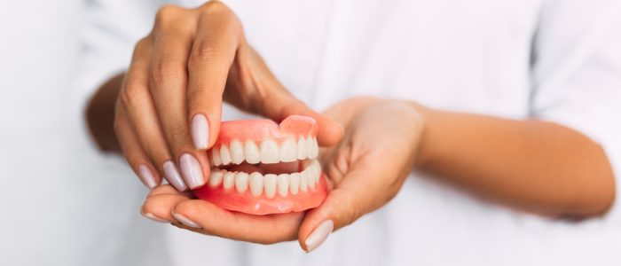 Young woman holding dentures in her hands